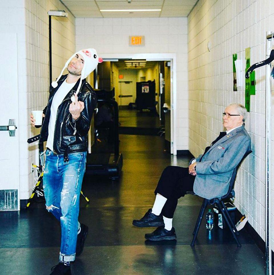 14. März 2017  Adam Levines neuestes Accessoire ist seine Mütze und die unflätige Geste dazu. Der Herr auf dem Stuhl wundert sich auch über das Benehmen.