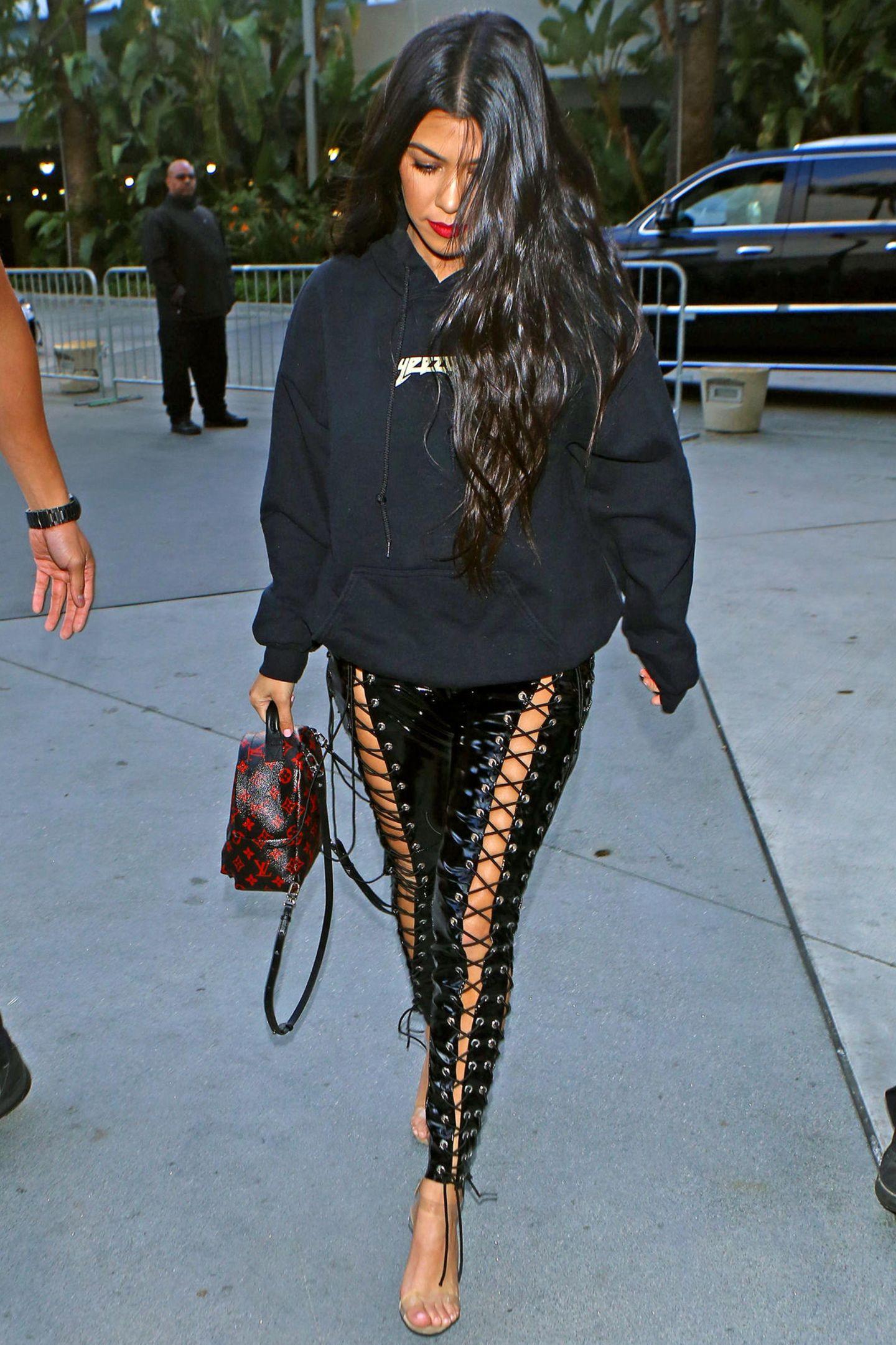 Kourtney Kardashian begleitet ihre Schwester Khloé zu einem Basketballspiel ihres Lovers, Tristan Thompson, in Los Angeles. Sie setzt dabei auf einen sportlich-schicken Look: Voluminöse Mähne und rote Lippen stehen in Kontrast zu ihrem übergroßen Hoodie von Schwager Kanye West. Ein besonderer Hingucker ist ihrer Lederhose zum Schnüren, die scheint nicht nur in der Kardashian-Jenner-Familie sehr beliebt zu sein...