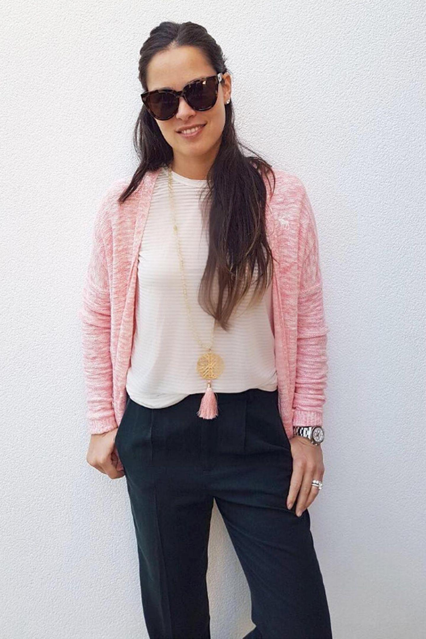 """Frisch in den Frühling! Ana Ivanovic schickt ihren Instagram-Fans dieses Bild ihres """"Outfit des Tages"""". Den rosafarbenen Cardigan kombiniert schön kontrastreich mit der dunkelblauen Hose. Und auch die Kette ist als Accessoire ist perfekt abgestimmt."""
