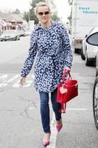 Reese Witherspoon könnte in der mit Veilchen übersäten, leichten Jacke und der knallroten Handtasche als Blickfang gar nicht frühlingshafter aussehen