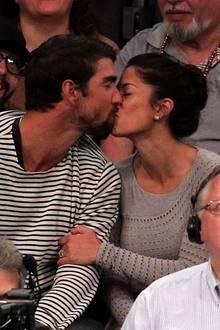 """Die """"Kiss Cam"""" hat diesmal Schwimmweltmeister Michael Phelps und seine Frau Nicole Johnson erwischt, die es bereitwillig mitmachen und küssen. Das Paar sitzt im Publikum beim Basketballspiel der Lakers."""