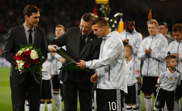 DFB-Präsident Reinhard Grindel überreicht Lukas Podolski vor der Partie gegen England ein Geschenk.