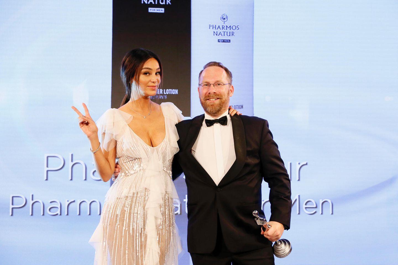 """TV-Liebling Verona Pooth gewinnt mit ihrer sympathisch-spritzigen Art das gesamte Publikum für sich. Sie überreicht Axel Klafs (CEO von Pharmos Natur) den Award in der Kategorie """"Men Concepts""""."""