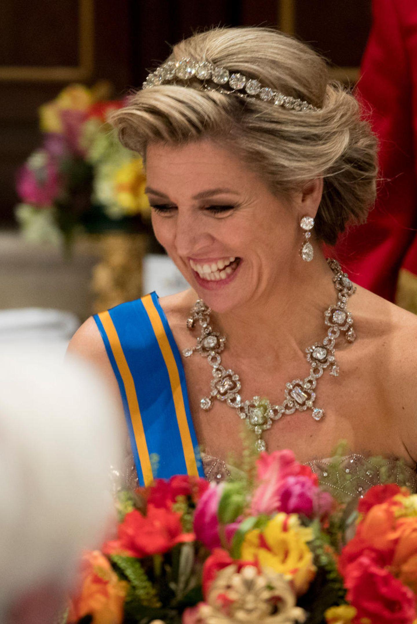 Bei dem Staatsbankett im königlichen Schloss richten sich Ende März alle Augen auf Königin Máxima, die mit ihrem funkelnden Schmuck nur so um die Wette strahlt. Ganz besonders fällt die hübsche Tiara auf, die ihrer Frisur den royalen Schliff gibt. Dabei war dieses Stück anfangs gar nicht als Diadem gedacht:  1879 erhält Königin Emma es in Form einer Kette. Erst ihre Tochter, Königin Wilhelmina, lässt es in den 30er-Jahren umgestalten. Seither ist es eines der Prachtstücke der Schmuckkollektion des niederländischen Königshauses.  In Kombination mit dem Collier erreichen die Karatzahlen beachtliche Höhe: Man kannte es vor allem von Königin Juliana, der Mutter von Máximas Schwiegermutter Beatrix. Es schlummerte also sehr lang in der königlichen Schatzkammer, ehe es an Máximas Hals ein Comeback feierte.