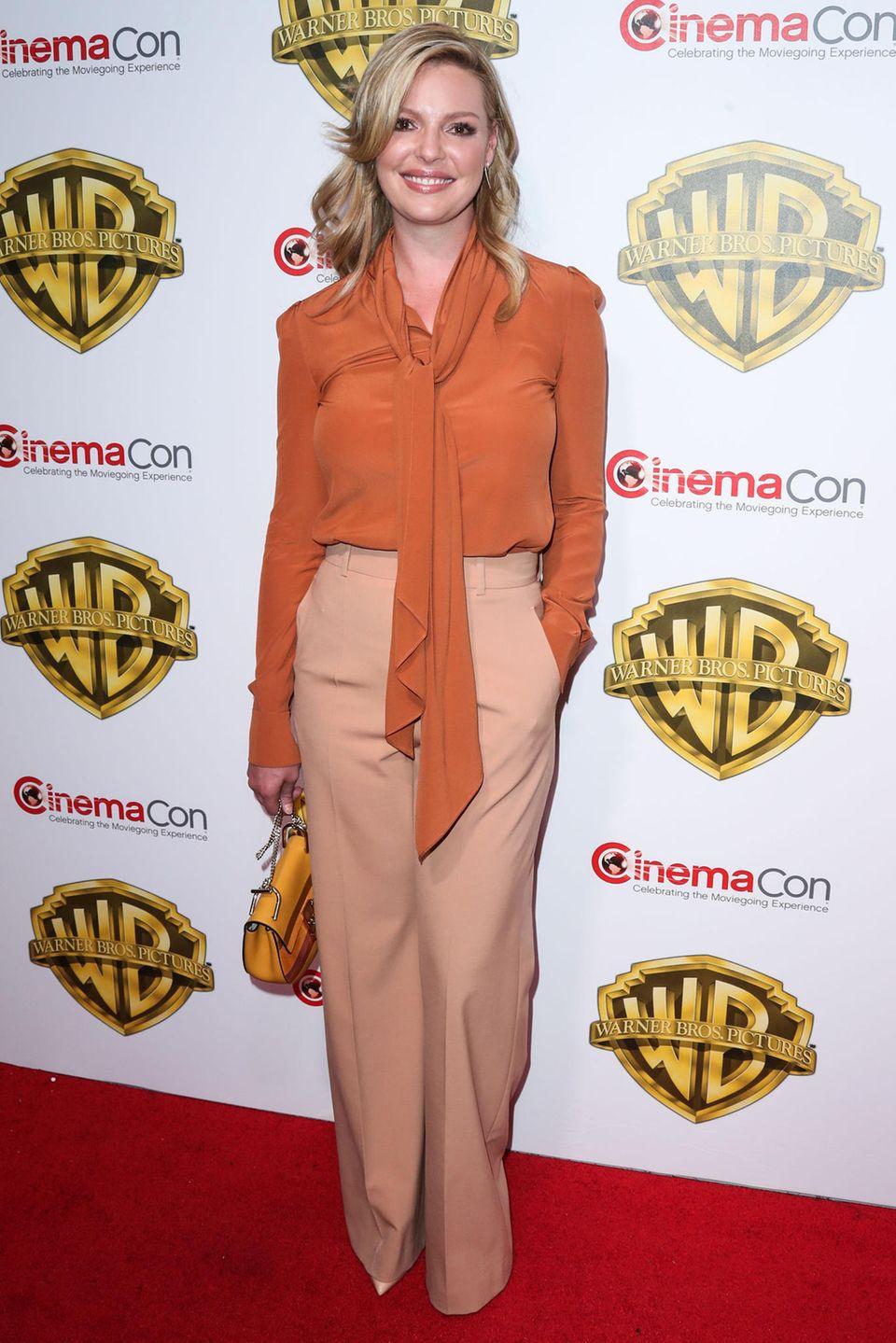 Katherine Heigl wirkt etwas blass in der orange Schluppenbluse und der cremefarbenen Marlenehose.