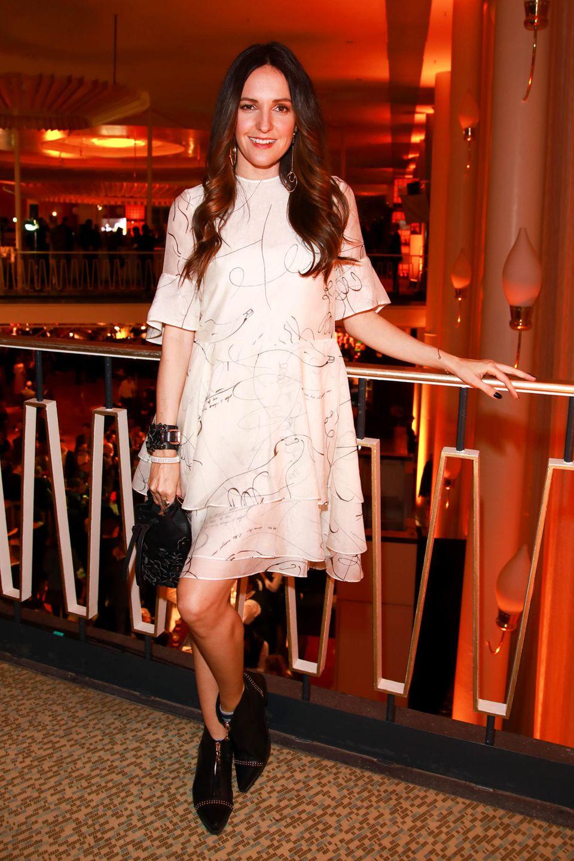 Auf der Aftershow-Party feiert Johanna Klum in einem romantischen Look. Ihr feenhaftes Flatterkleid hebt sie durch einen coolen Kontraste mit Leder-Accessoires und Boots hervor.
