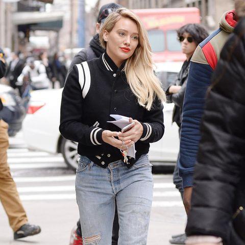 Hilary Duff mixt gleich drei Trends in einem Outfit: Collage-Jacke, zerrissene Mom-Jeans und weiße Stiefeletten.