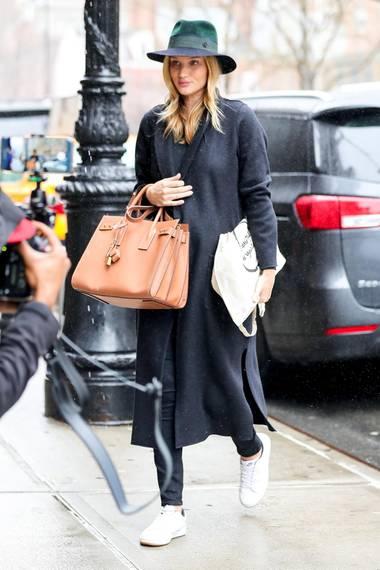 """Das perfekte Shopping-Outfit für einen regnerischen Tag in New York: Ein langer, grauer Mantel, ein Fedora Hut und als Hingucker die """"Sac De Jour""""-Tasche des Labels Saint Laurent für 2450 Euro, die das wachsende Babybäuchlein stylisch versteckt. Rosie Huntington-Whiteley weiß eben, wie es geht!"""