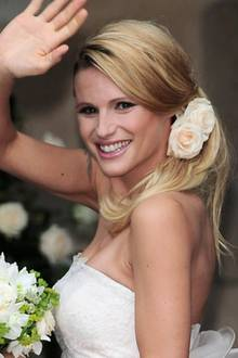 Michelle Hunziker verwandelt sich an ihrem Hochzeitstag in eine besonders romantische Braut. Dafür sorgen in erster Linie die Rosen, die ihre seitliche One-Shoulder-Frisur verzieren. Das Volumen im Ansatz lässt sie außerdem natürlich erscheinen.