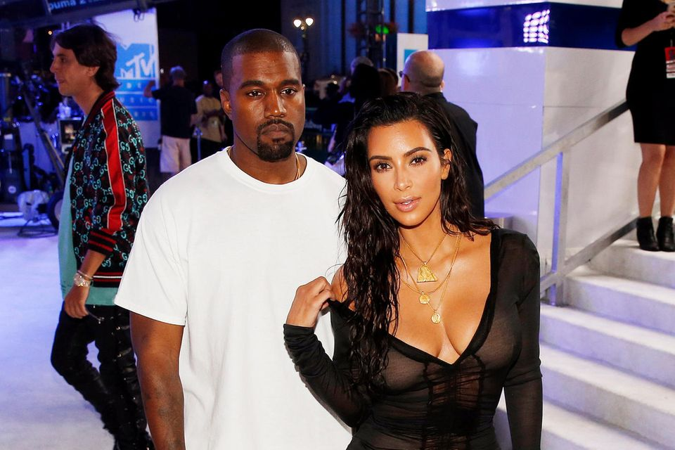 Kim posiert vorne sexy für die Fotografen und Kanye hält ihr den Rücken frei.