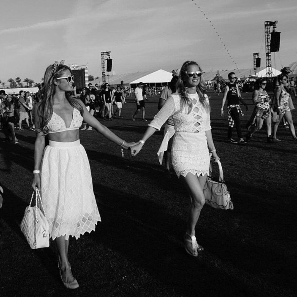 Ganz in Weiß und Hand in Hand genießen die Hilton-Schwestern Paris und Nicky das Festival.