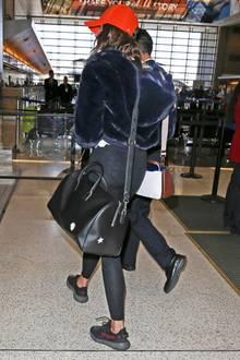 """Bequemer Flugzeuglook hin oder her, dieses Malheur darf einem Unterwäsche-Model eigentlich nicht passieren: Durch die schwarzen Leggins sieht man deutlich den Sternchen-Schlüpfer dieses """"Victoria's Secret""""-Engels."""