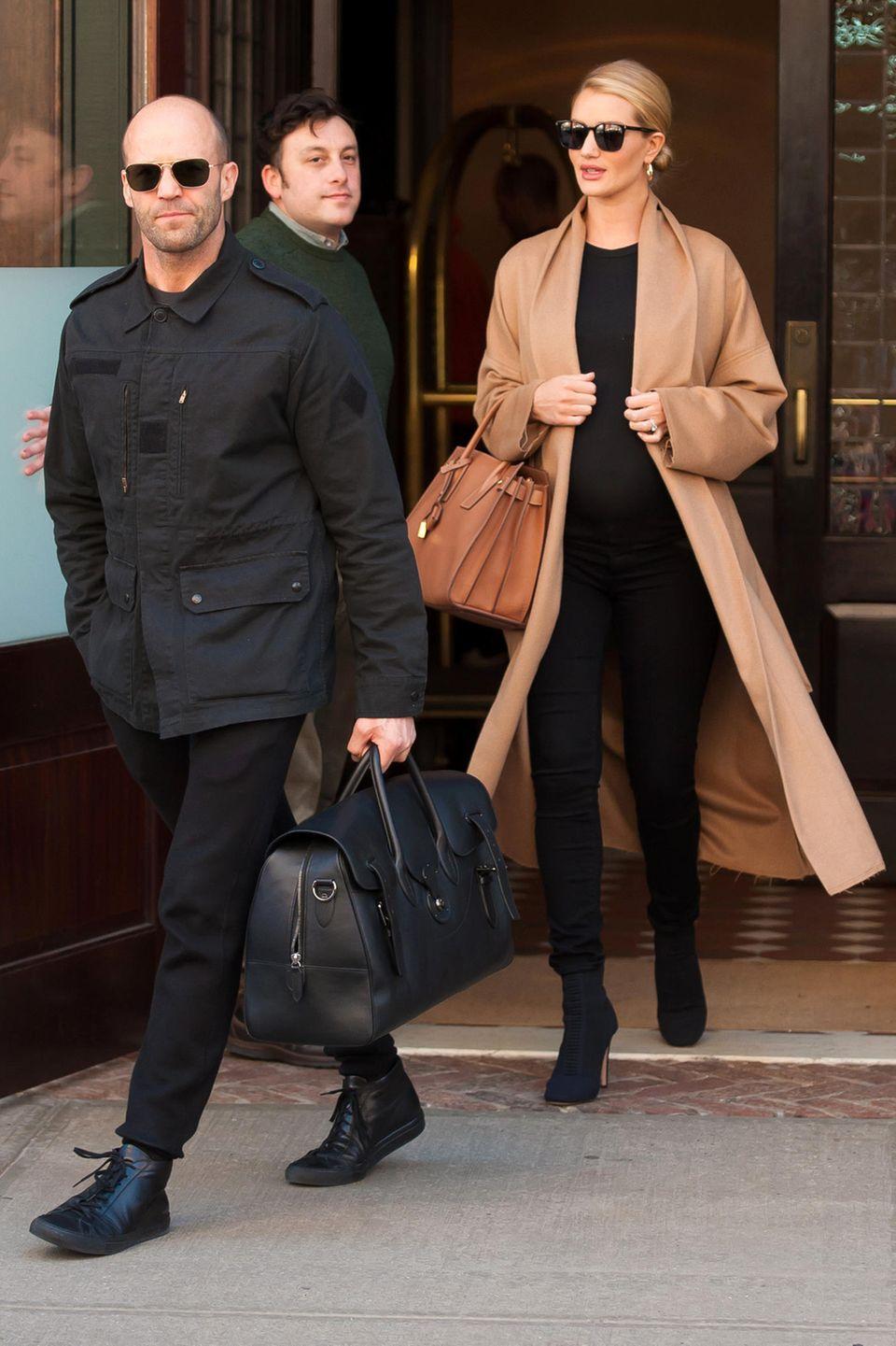 Nur Rosies Kamelhaarmantel ist ein hellerer Lichtblick, ansonsten versteckt das Supermodel auch hier ihren Babybauch im lässigen, schwarzen Outfit. Und das sogar im Partnerlook mit ihrem Verlobten Jason Statham.
