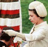 Als Queen Elizabeth ihren Sohn, Prinz Charles, in sein Amt als Fürst von Wales einführt, trägt sie eine traditionelle Kopfbedeckung, die passend zu ihrem Mantel mit Perlen bestickt ist.
