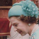 Ein wunderschönes Bouquet befindet sich am hinteren Teil von dem Hut, den Queen Elizabeth zu der Hochzeit von Charles und Diana trug.