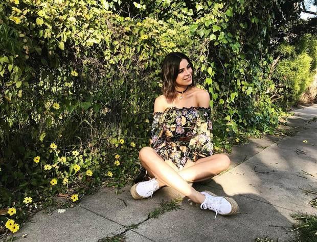 Lena Meyer-Landrut wird von ihren Fans auf Instagram immer wieder wegen ihrer angeblich zu dünnen Figur kritisiert. Dennoch lässt sich die Sängerin ihre gute Laune nicht verderben und schickt lächelnde Fashion-Grüße aus L.A. Warum Lena die sonnige Stimmung in L.A. ausgerechnet auf einem Gehweg genießt, wissen wir nicht, aber im floralen, schulterfreien Carmen-Look und weißen Bast-Plateau-Sneaker sieht sie dabei ganz bezaubernd aus.