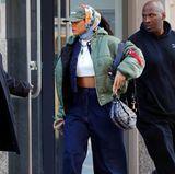 """Momentan steht Rihanna voll auf die Bomberjacken von Vetements. Daher besitzt sie nicht nur ein Modell in Schwarz, sondern auch in Olivgrün. Zu diesem Oversized-Stück kombiniert sie einen Denim-Zweiteiler von Dries Van Noten, ein weißes Designer-Croptop, ein Seidentuch von Gucci und Palteau-Sneaker von """"FENTY x Puma"""". So gemütlich dieser Look auch ist, kann er vom Preis her glatt mit einer Red-Carpet-Robe mithalten. Etwa 3.500 Euro muss man für den Look hinlegen. Und dann hat man nicht einmal RiRis Schmuck und die Tasche von Dior."""