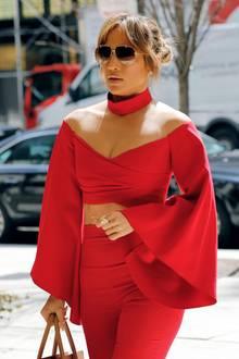 """Wie ein Bauchfrei-Look besonders edel wirkt, zeigt uns Jennifer Lopez. Sie wählt ein kurzes Oberteil, das durch elegante Trompetenärmel besticht und kombiniert es zu Choker und High-Waist-Hose im selben Ton. So verwandelt sie sich zur """"Lady in Red""""."""