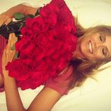 Für mich soll's rote Rosen regnen: Heidi Klum lässt sich freudestrahlend mit einem riesigen Blumenstrauß ins Bett fallen.