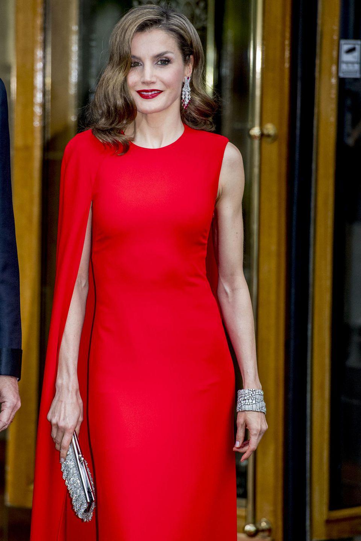 In einem roten Kleid der britischen Designerin Stella McCartney macht sich Königin Letizia von Spanien auf den Weg zur Geburtstagsparty von König Willem-Alexander. Durch den raffinierten One-Shoulder-Schnitt wird nur einer ihrer trainierten Arme durch einen Cape-Ärmel verdeckt. Außerdem trägt sie tollen, silbernen Schmuck und eine silberne Clutch.
