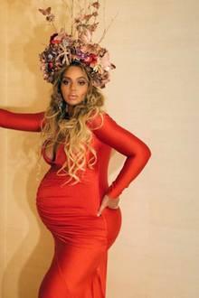 """Auf der """"Wearable Art Gala"""" in Los Angeles bezaubert Beyoncé in einem langen, figurbetonten Kleid in Orangerot vom Label Stello. Der tiefe Ausschnitt zeigt ihr Mega-Dekolleté, süße Raffungen setzen ihre Zwillingskugel gekonnt in Szene. Ihrem Spitznamen entsprechend trägt """"Queen Bey"""" eine aus Kunstblumen gebastelte Krone, die mit Schmetterlingen und Libellen geschmückt ist."""