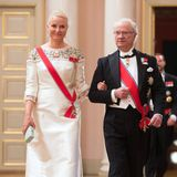 """Prinzessin Mette-Marit, begleitet vom schwedischen König Carl Gustaf, bezaubert im floral bestickten, schweren, weißen Seidenkleid mit roter Schärpe. Auch wenn ihre Tiara von vorne kaum zu sehen ist, sie trägt die """"Vifte""""-Tiara weiter hinten im Haar, das """"Fächer""""-Diadem, das sie genauso gut auch als Collier tragen kann."""