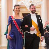 """Wunderschön in Royalblau (Elie Saab) schwebt Prinzessin Victoria mit Erbgroßherzog Guillaume von Luxemburg zum festlichen Dinner. Das Kleid trug sie bereits zur Nobelpreis-Verleihung 2010. Dazu trägt sie ihre geliebte """"Baden Fringe""""-Tiara, auch bekannt als Sonnenstrahl-Tiara, die mit 47 strahlenförmig angeordneten Diamant-Reihen besonders glamourös glitzert."""