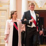 """Großherzogin Maria Teresa von Luxemburg, hier an der Seite von König Willem-Alexander, hat sich mit ihrem roséfarbenen, bodenlangen Mantel über dem schwarzen Kleid für einen modernen Luxus-Look von Yves Saint Laurent entschieden. Dazu trägt sie die """"Belgian Scroll"""