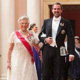 Prinzessin Astrid von Norwegen im weißen Spitzenkleid und der Türkis-Tiara von Königin Maud scheint mit Prinz Nikolaos von Griechenland einen amüsanten Begleiter gefunden zu haben.
