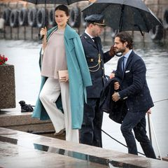 """Nach einem Mini-Cruise mit Lunch verlassen Prinzessin Sofia und Prinz Carl-Philip bei strömendem Regen das Königsschiff """"Norge"""". Das Schmuddelwetter kann der schwangeren Prinzessin jedoch nichts anhaben: Sie hat sich einen grünen Mantel übergeworfen und trägt Stiefeletten zur weiten Marlenehose. Das cremefarbene Cape mit seitlicher Knopfleiste schützt ihr Babybäuchlein vor Nässe und Kälte."""