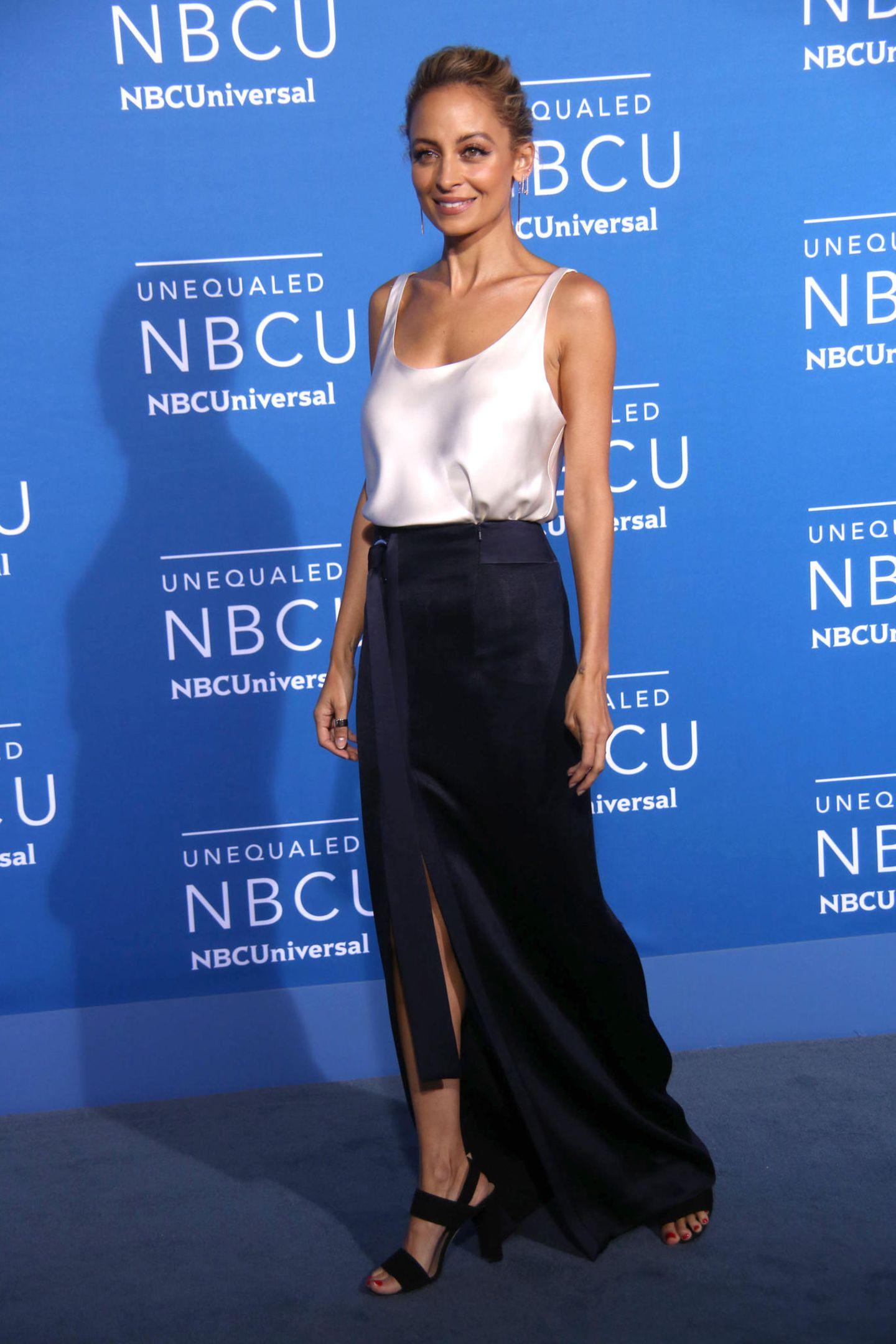 Nicole Richie betont ihre dünne Silhouette mit Nude-Seidentop und dunklem, geschlitztem Rock.