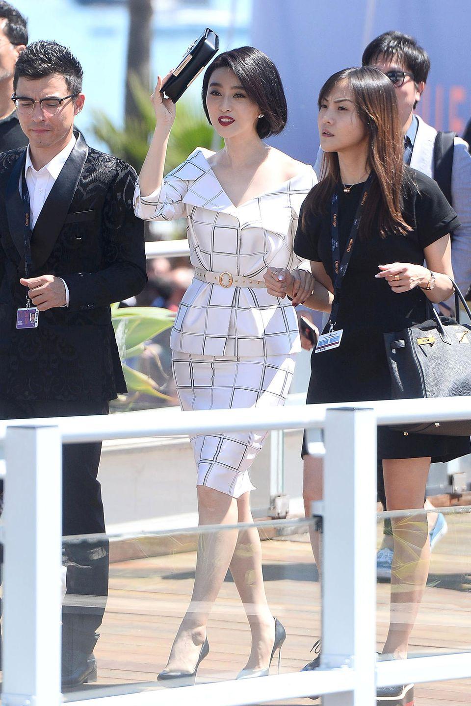 Fan Bingbing ist im stylischen, weißen Karo-Kostüm eher damit beschäftigt, ihre sehr helle Haut vor den Sonnenstrahlen in Cannes zu schützen.