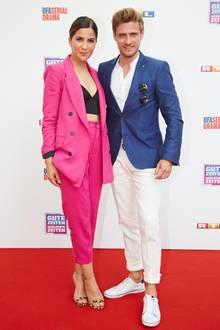 Neuzugang Chryssanthi Kavazi und Jörn Schlönvoigt, der schon seit Jahren dabei ist, posieren gemeinsam auf dem roten Teppich. Sie entscheidet sich für einen pinken Anzug unter dem sie nur einen schwarzen BH trägt, er trägt zu seinem blauen Jackett eine weiße Hose und Sneaker.