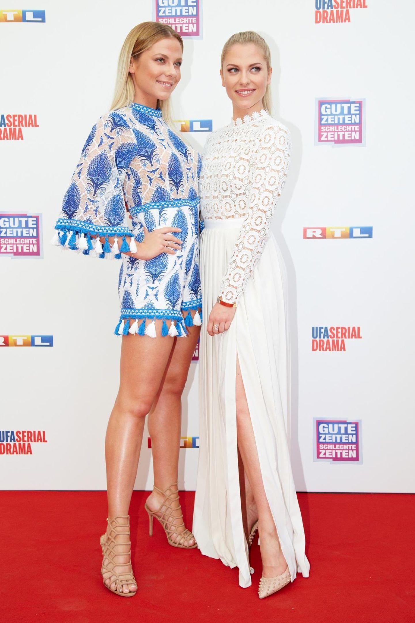 """Das doppelte Lottchen in der Glamourversion: Valentina Pahde (rechts) alias """"Sunny"""" bekommt auf dem roten Teppich Unterstützung von ihrer Zwillingsschwester Cheyenne, die einen Jumpsuit mit Fransen und blauem Muster trägt. Valentina hat sich für ein weißes Kleid des Labels """"Selfportrait"""" entschieden."""