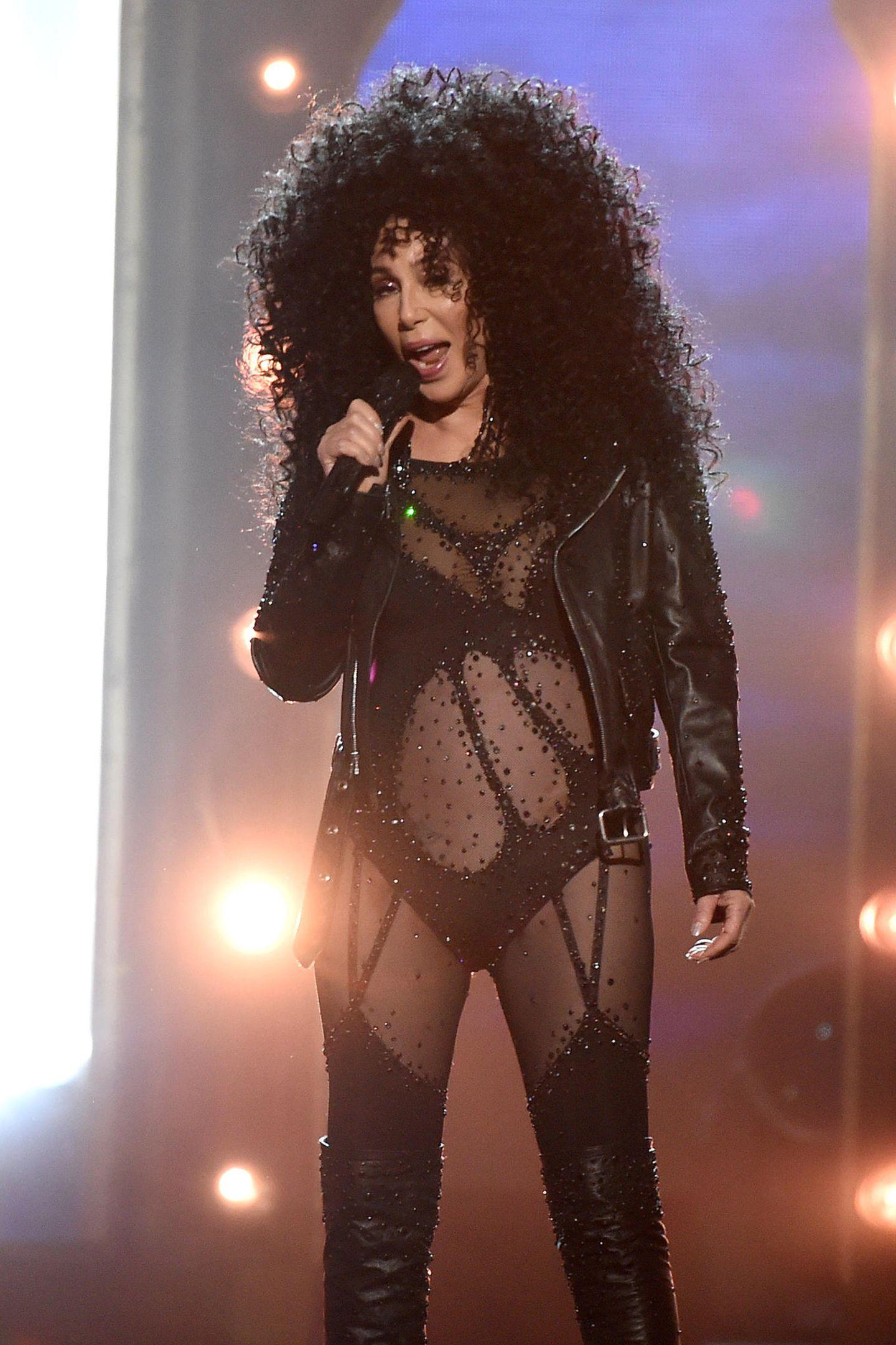 """Die sexy Offensive bei den """"Billboard Music Awards"""" setzt Cher auch bei ihrem zweiten Outfit fort. Im Transparent-Body mit Strapsen und Overknees performt sie, dass die XXL-Locken nur so beben. Diesen Look trug sie ursprünglich bei den VMAs in 2010."""