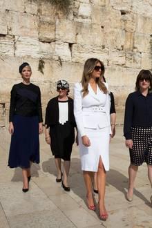 Als erster US-Präsident pilgert Donald Trump zur Klagemauer in Jerusalem. Immer an seiner Seite: seine Frau Melania und seine Tochter Ivanka (ganz links). Melania entscheidet sich für ein komplett weißes Outfit; sie trägt einen knielangen Rock mit kleinem Schlitz und einen Blazer, der dank eines unauffälligen Gürtels ihre Taille betont. Einzig farbiges Detail sind ihre rot-gemusterten Schuhe.