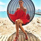 """Lasziv posiert Steffi in diesem Hängesessel am Strand in Südfrankreich. So kommt das knallige Rot ihres roten Off-Shoulder-Kleides vom australischen Label """"AliceMcCall"""" perfekt zur Geltung."""