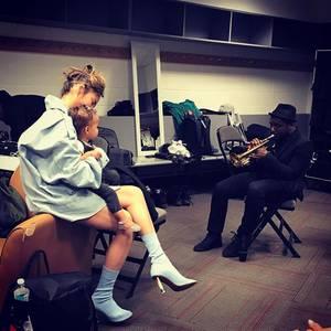 Chrissy Teigen mit Töchterchen Luna backstage beim Konzert von John Legend: Die beiden lauschen einem Trompeter, der hinter der Bühne ein paar Töne für sie spielt.