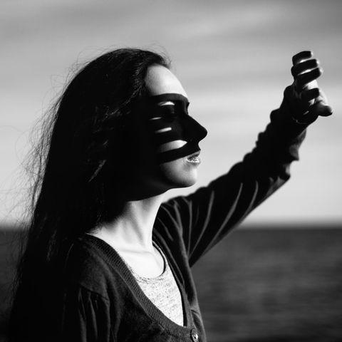 Frau hält Hand gegen das Sonnenlicht