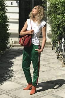 Sue kombiniert ihre Sock Boots zu grüner Trainingshose, einem schlichten weißen Shirt und burgunderfarbenem Rucksack.