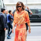 Ein sommerlich-stylischer Blickfang ist auch Victoria Beckhams leuchtend orangefarbene Ensemble aus luftiger Bluse und schön schwingendem Faltenrock.