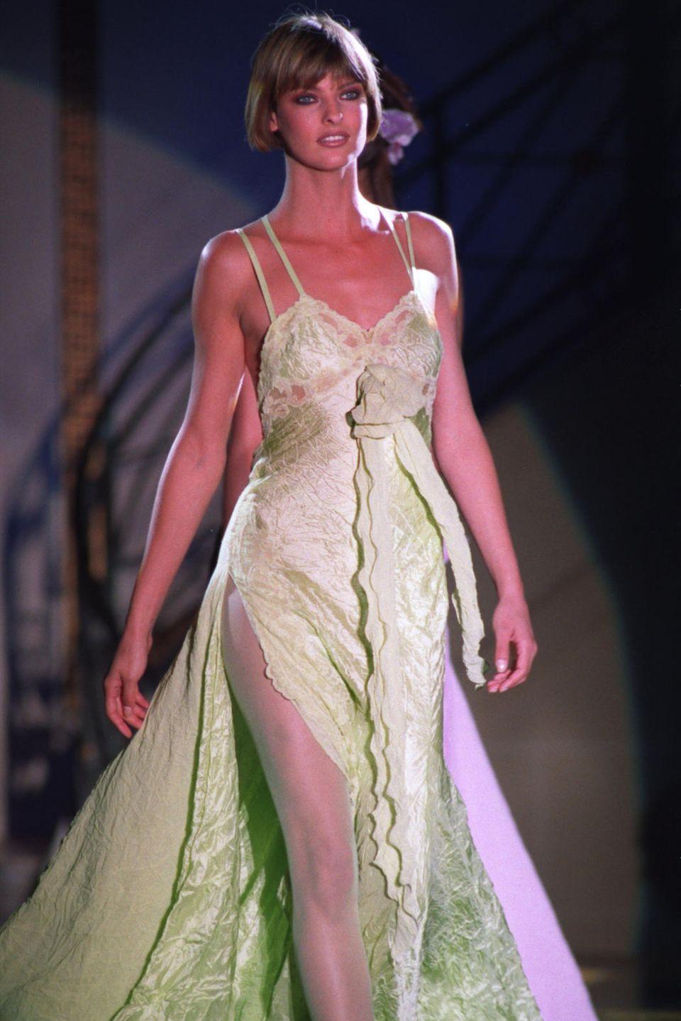 """Ohne Linda Evangelista würde es den Begriff """"Supermodel"""" wahrscheinlich gar nicht geben. Schließlich ist die Mitte der 1980er-Jahre absolute Vorreiterin in diesem Gebiet. 1984 landet sie ihre ersten Cover-Shootings, wenige Jahre später betritt sie für Karl Lagerfeld den Catwalk. Als Gianni Versaces Muse läuft sie hier in 1993 über den Laufsteg."""