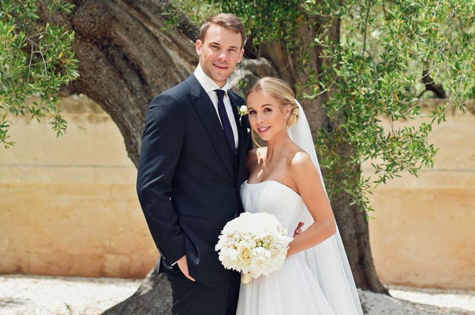 Mai  Das frisch vermählte Ehepaar Manuel Neuer und Nina Weiss: Nina trägt eine Traumrobe mit langer Schleppe in Weiß und Manuel ist ganz elegant und traditionell im schwarzen Anzug erschienen.