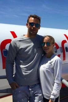 """Die frisch Vermählten, Manuel Neuer und Nina Weiss, sind wahrscheinlich auf dem Weg in die Flitterwochen. Für den Flug tragen sie Sweatshirts mit den Aufschriften; """"He's mine"""" und """"She's mine"""" (dt. Er/Sie gehört mir)."""