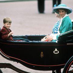 1988:Prinzessin Diana legt bei dem Event mal wieder einen Wow-Moment hin. Als sie zusammen mit Sohnemann William in einer Kutsche Richtung Buckingham Palace fährt, stiehlt sie in ihrem azurgrünen Ensemble allen die Show.