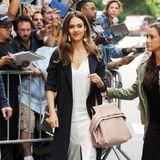 Jessica Alba kombiniert ihr weißes Kleid zwar kontrastreich mit dunkelblauem Sommermantel, dem Pastell-Trend folgt sie aber auch mit ihrer altrosafarbenen Handtasche.