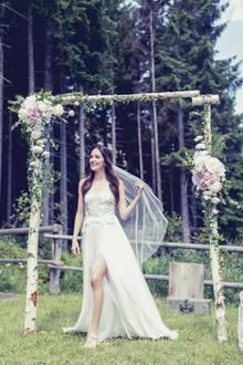 Bei Johanna Klum stehen alle Brautkleid-Zeichen auf Sommer. Ihre Traumrobe von Kaviar Gauche besticht durch hübsch fallende Stoffe, einen hohen Beinschlitz und einen luftig leichten Schnitt. Den eleganten Hippie-Look setzt die hübsche Moderatorin an ihren Füßen fort. Sie trägt flache Zehensandalen mit Blumendekor.