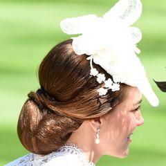 Auf dem Kopf trägt sie einen weißen Faszinator mit Blumendekoration. Ihr brünettes Haar ist zu einem eleganten Chignon zusammen geknotet.