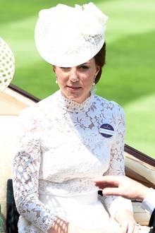 Zu dem weißen Kleid, das in jedem Fall kürzer ist, als das aus dem Vorjahr, trägt sie dezente Perlenohrringe. Das Kleid ist jedoch hochgeschlossen und hat einen Kragen aus Spitze.