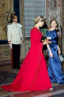 In einer roten Robe mit Schleppe und weiten Ärmeln begleitet Königin Máxima Laura Mattarella, die Frau des italienischen Präsidenten, zum Staatsbankett im Quirinalspalast.